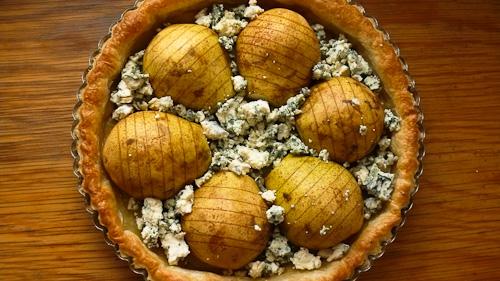 Крушите се нареждат върху полуготовото тесто, поръсва се сиренето