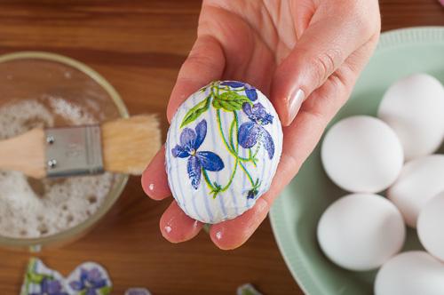 Яйцето със салфетката се намазва с белтък