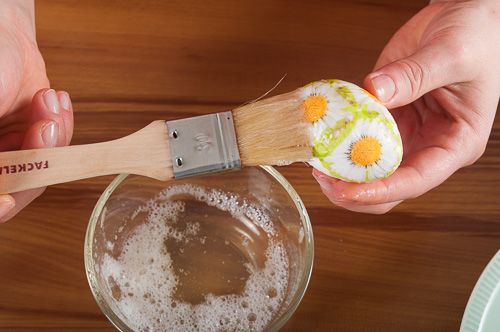 Изрязани мотиви от салфетката се залепят с белтък върху яйцето