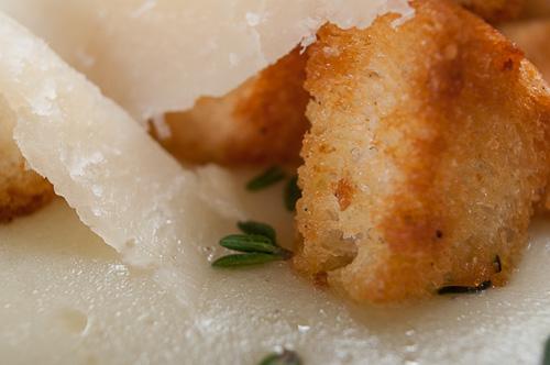 Детайл от крем супата с крутони, люспи пармезан и мащерка