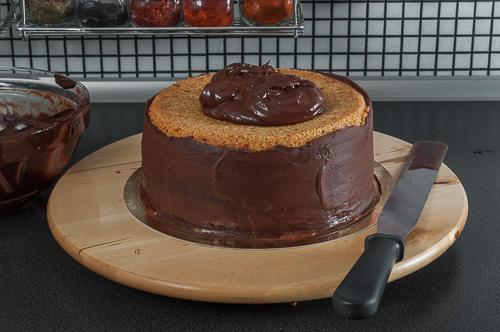 Стените на тортата се покриват с шоколадов ганаш