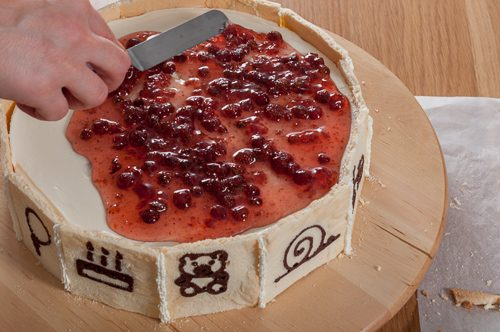 Повърхността на тортата се покрива със слой сладко от горски ягоди