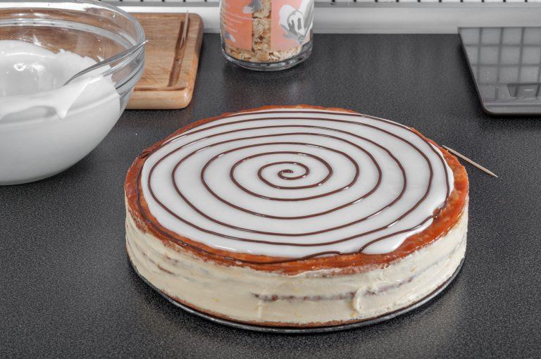 Разстеленият фондан върху тортата с направена спирала от шоколад