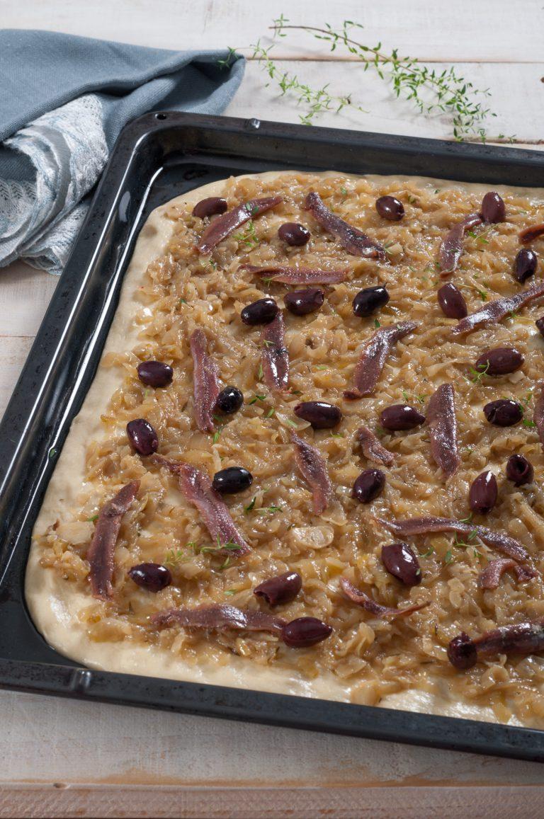 Аранжираното тесто с карамелизирания лук, аншоата и маслините, поръсени с допълнително мащерка