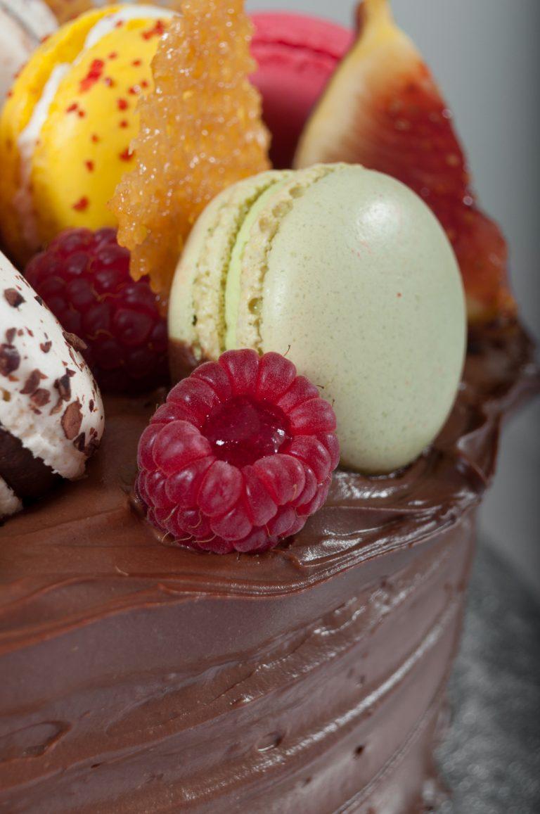 Детайл от декорацията на шоколадова торта с френски макарони и плодове