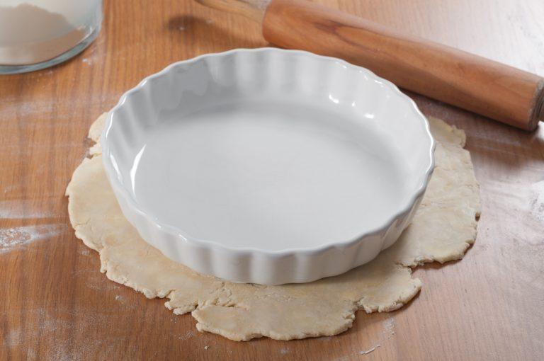 Налагане на формата за пай над тестото, за да се прецени размера