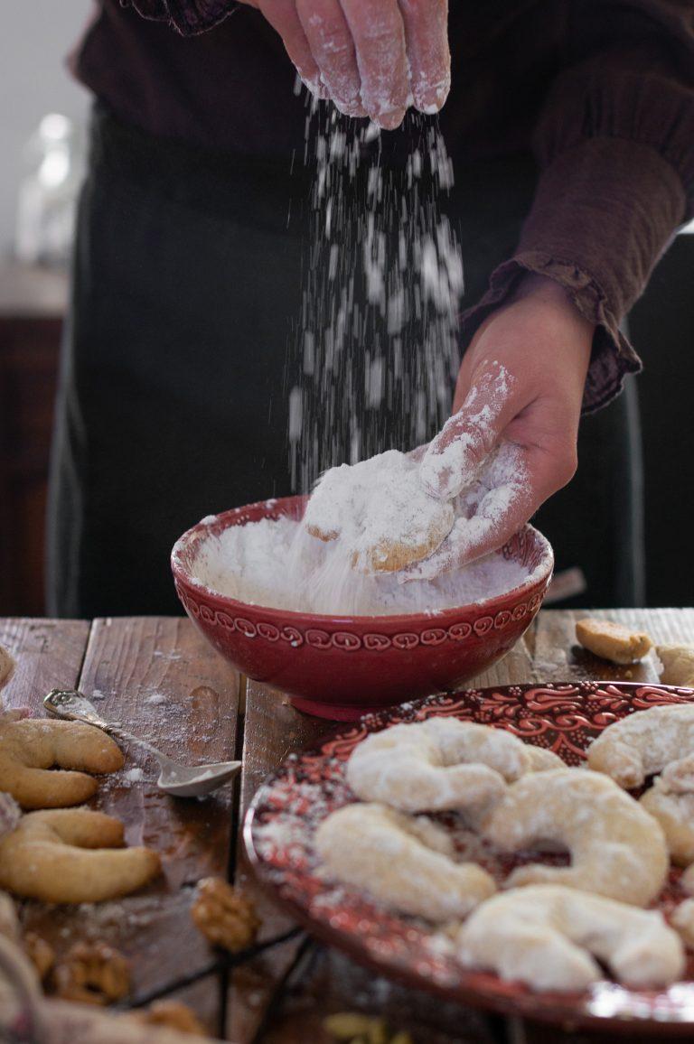 Поръсване на ръка на изпечените сладки с ванилова пудра захар