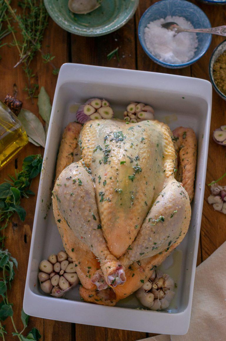 Подготвено за печене цяло пиле, овкусено с билки и масло