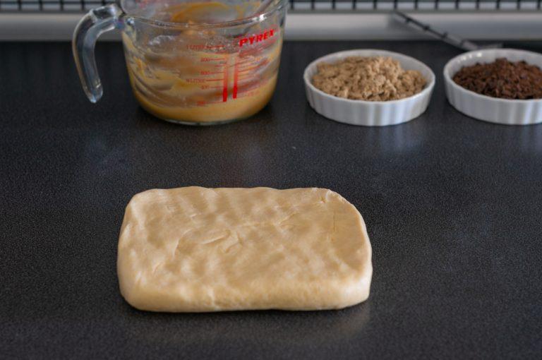 Едната част от охладеното тесто се слага върху плота