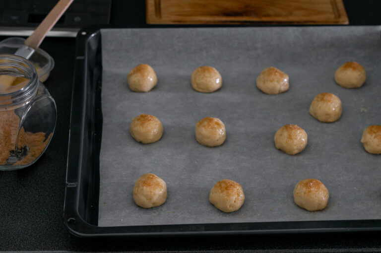От тестото се правят топчета, намазват се с яйце и се поръсват със захар