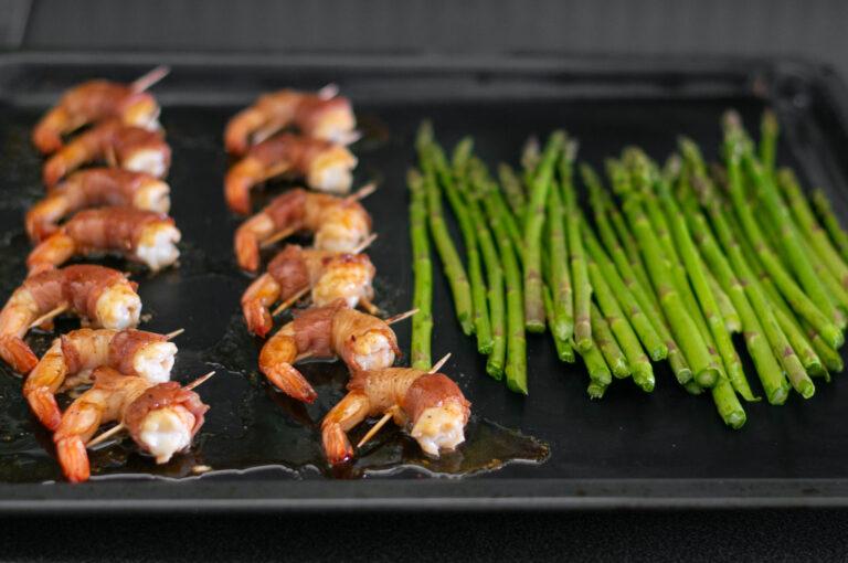 Добавените аспержи към скаридите в бекон по средата на печенето