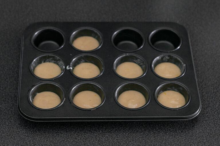 Тесто за мадлени шприцовано във форми за мини мъфини