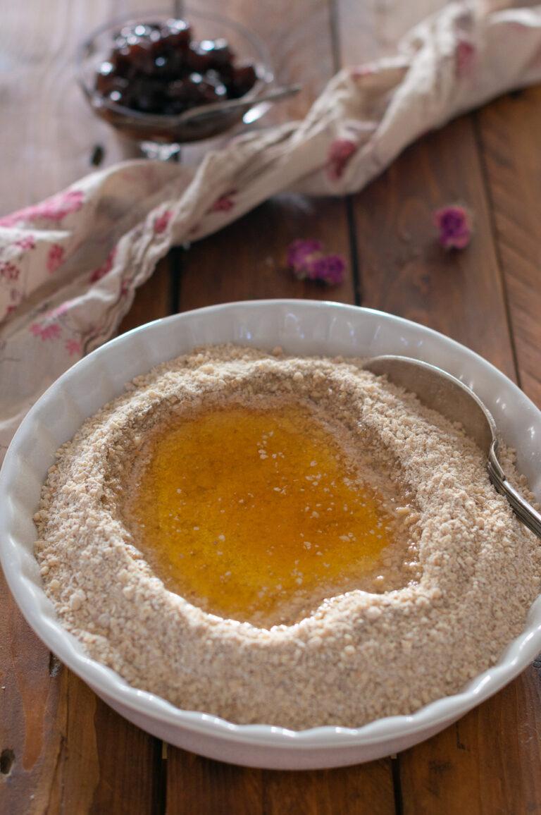 Добавяне на течните съставки в сместа със сухите за постни овесени сладки с череши и шоколад