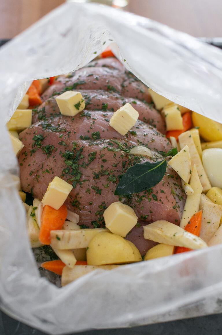 Сложените пуешко филе, зеленчуци и масло в плика за печене