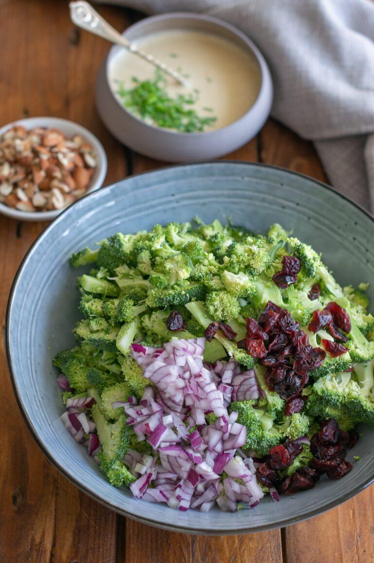 Нарязани броколи, червен лук и супени червени боровинки за салата от броколи