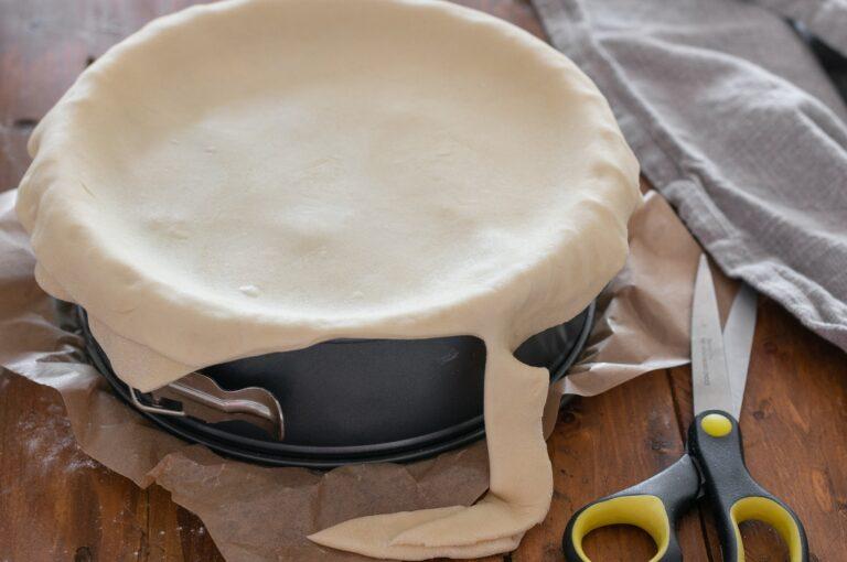Поставяне на горната кора върху пая и изрязване на излишното тесто